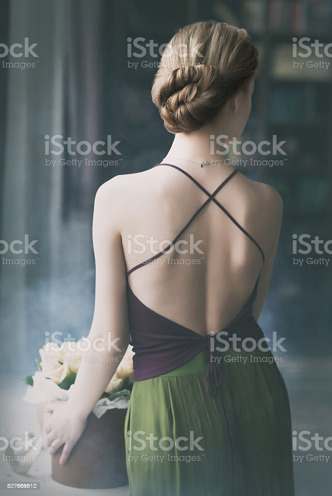 Young romantic woman staying with her back beside the window stock photo