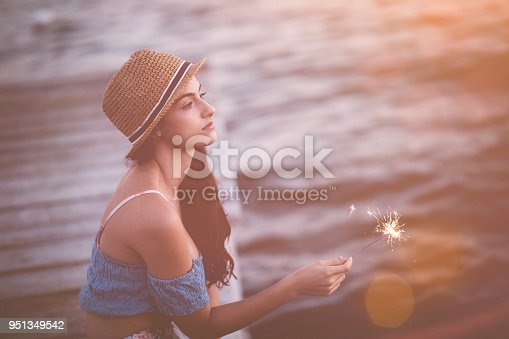 Young hipster girl with sparklers relaxing on wooden pier by the sea on summer holidays