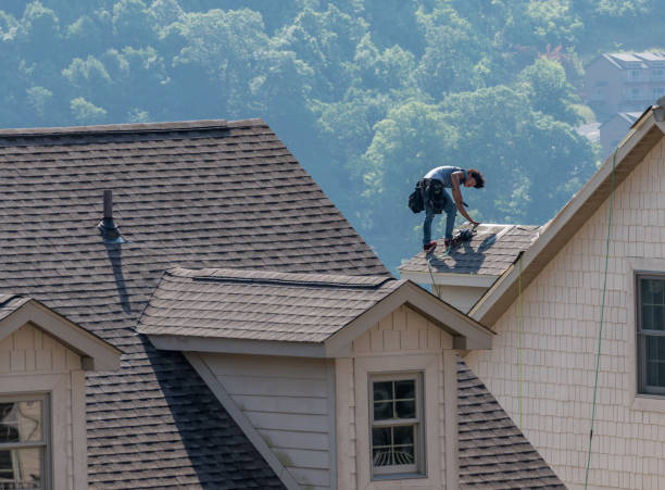 Young roofing contractor nailing shingles on a roof high above the ground stock photo
