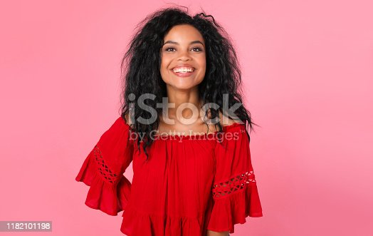 857924506 istock photo Young rose. Magnificent African American lady in a red blouse is laughing while standing right in front of the camera. 1182101198
