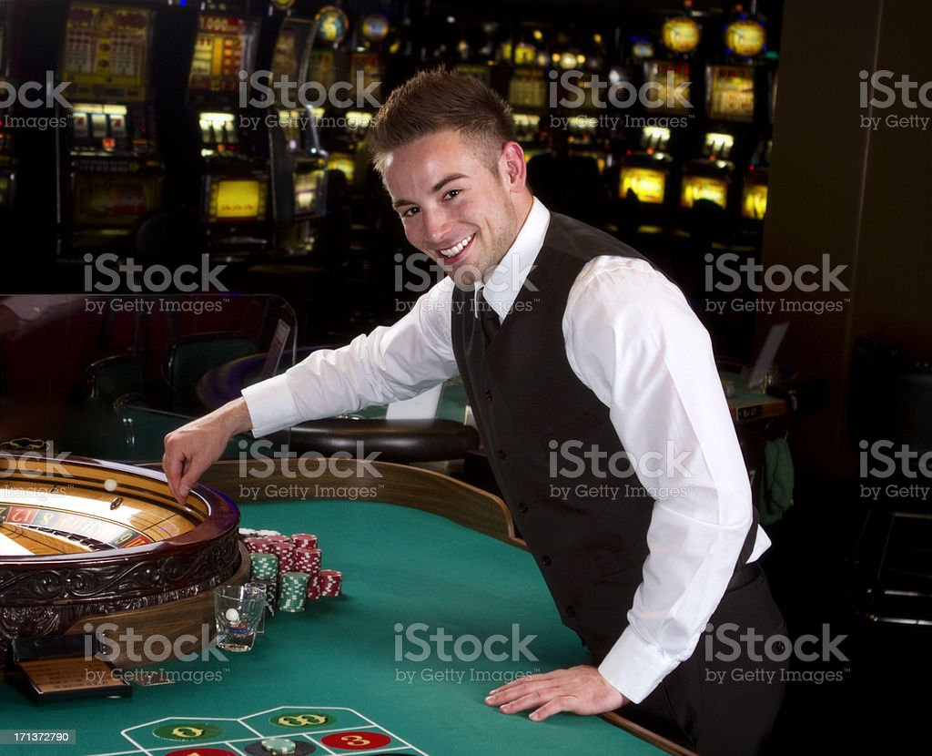 Young Roulette Dealer In A Casino stock photo