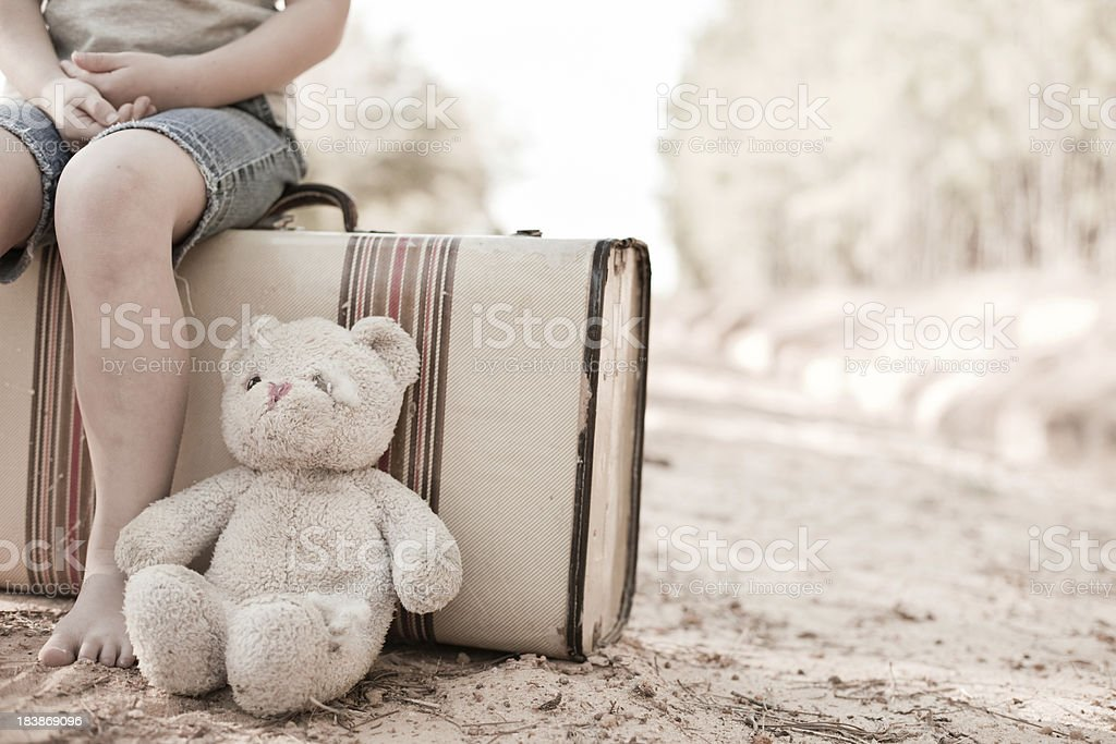 Young Runaway Girl Sitting on Suitcase with Old Teddy Bear royalty-free stock photo