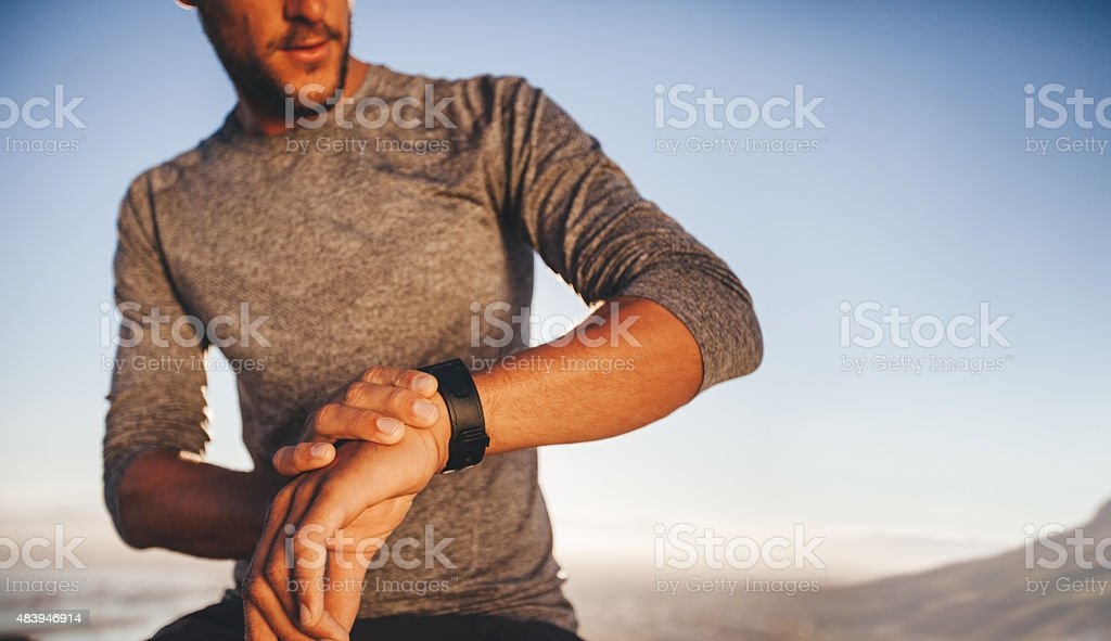 Young runner checking the time on his wristwatch stock photo