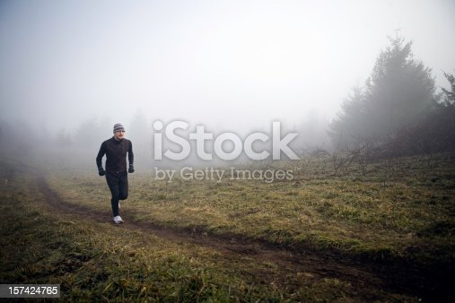 A young native Alaskan man runs up a small hill on a foggy morning.  Horizontal with copy space.