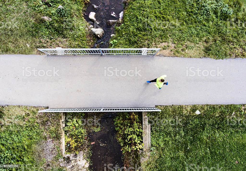 Young runner on a bridge above stream . Aerial view. – Foto