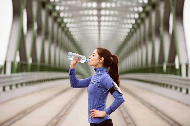 young runner resting, drinking water on green steel bridge - armband water stock-fotos und bilder