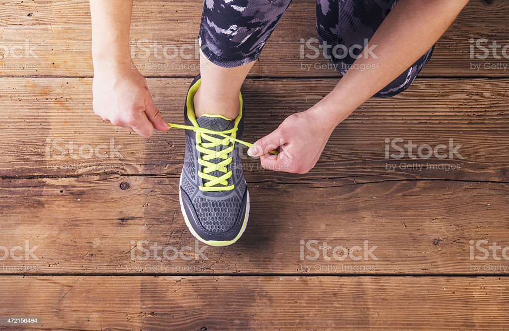 Young runner tying her shoes on a wooden floor stock photo