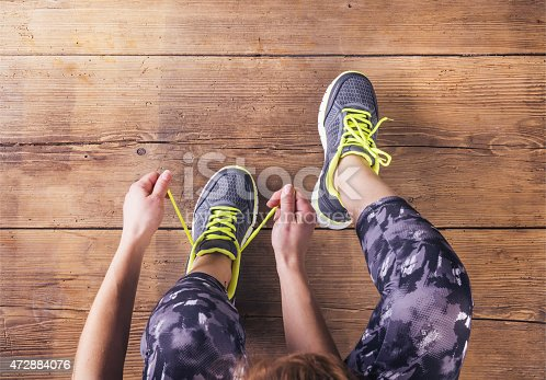istock Young runner tying her shoes 472884076