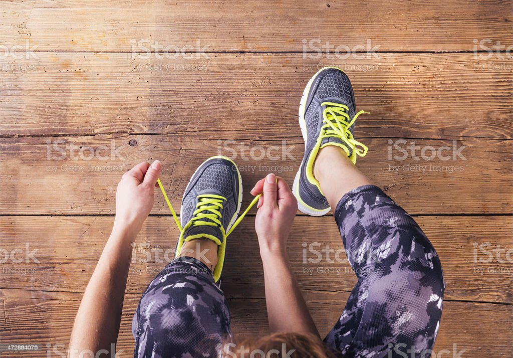 Young runner tying her shoes stock photo