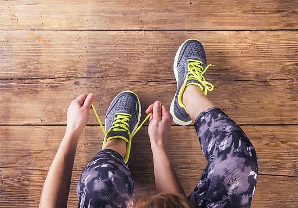 junge läufer binden ihre schuhe - schnürsenkel stock-fotos und bilder