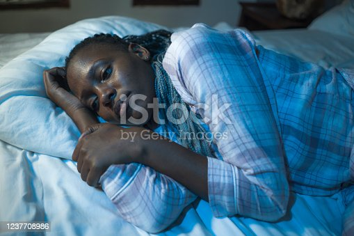 617364644 istock photo young sad and depressed black afro American woman lying on bed at home unhappy and sleepless at night feeling overwhelmed suffering depression problem and insomnia 1237708986