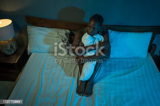 617364644 istock photo young sad and depressed black afro American woman lying on bed at home unhappy and sleepless at night feeling overwhelmed suffering depression problem and insomnia 1237709991