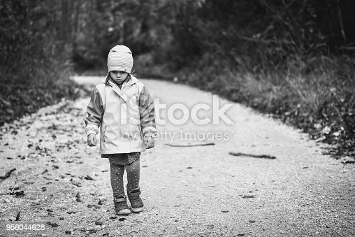 istock Young sad girl child is walking alone on country road. 956044628