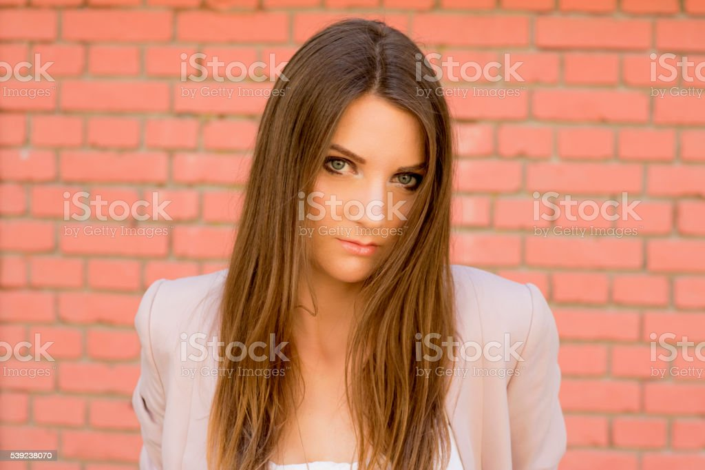 Young sad girl standing near the wall outdoors. Sadness royalty-free stock photo