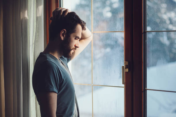 Young sad mad sitting by the window stock photo