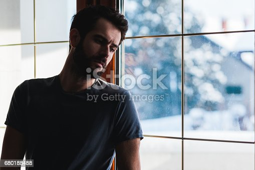 istock Young sad mad standing by the window 680188488