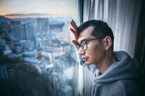 Young sad man by the window stock photo
