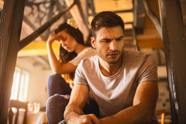 Young sad man having relationship difficulties with his girlfriend. stock photo