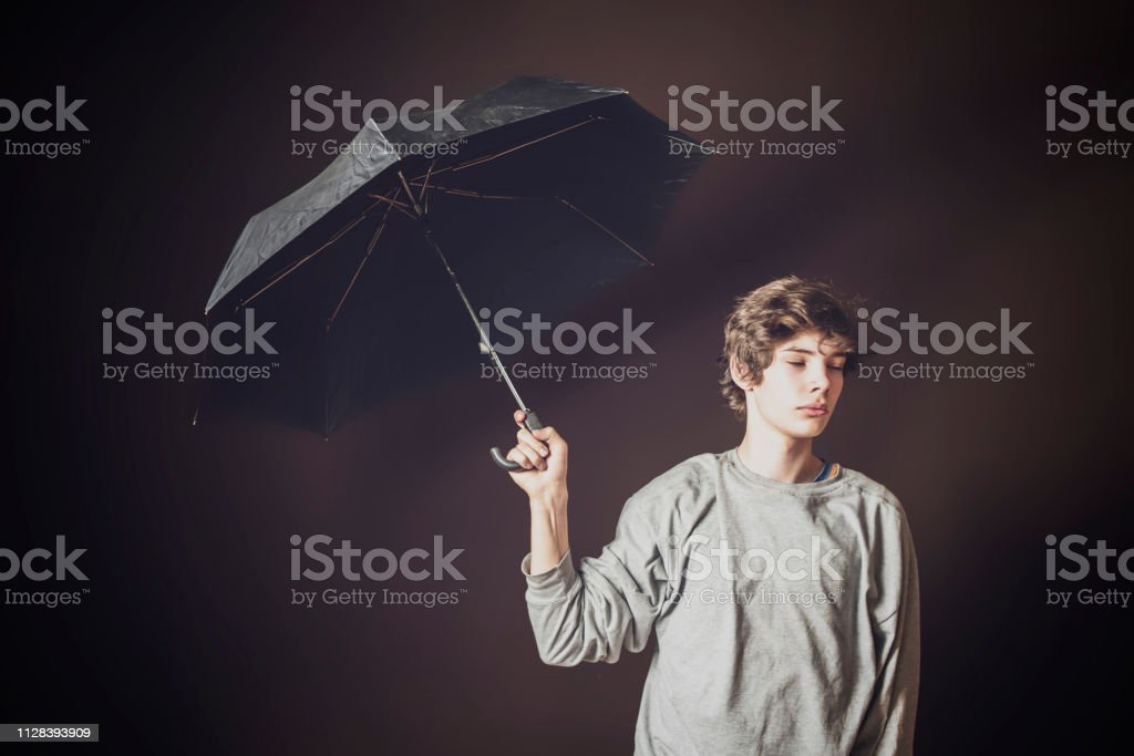 young sad man hold umbrella in bad weather on dark background