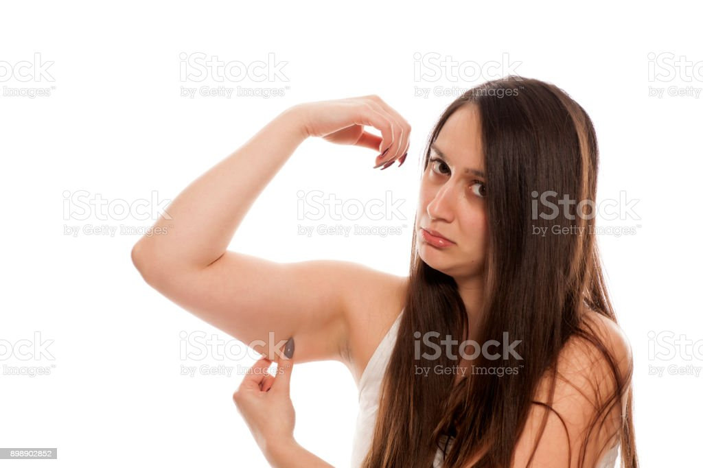Young sad woman shows fat on her hands stock photo
