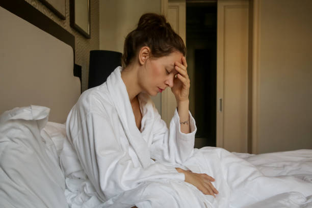 Junge traurige Frau im Bett sitzen, Depression, Angst, Beziehungsschwierigkeiten, Migräne oder Morgenkrankheit Konzept – Foto