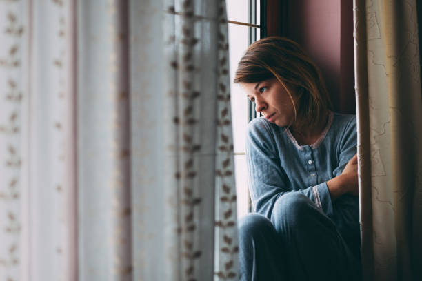 Young sad woman sitting on the window stock photo
