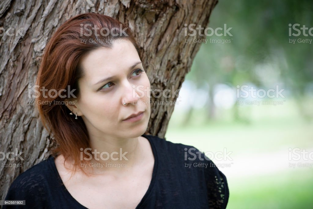 Young sad woman takes a break in the park - foto stock