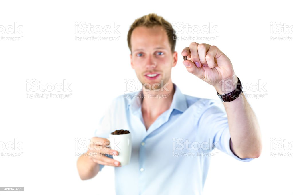 Young salesman holding cup and coffee beans stock photo