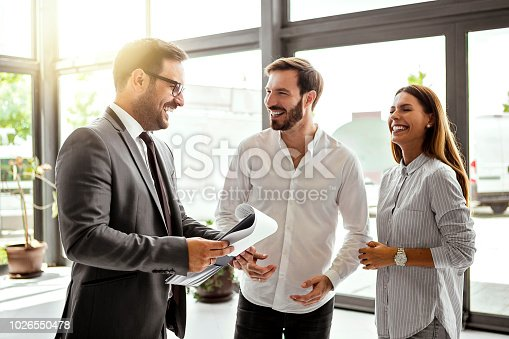 988321834 istock photo Young salesman selling a car to as young couple 1026550478