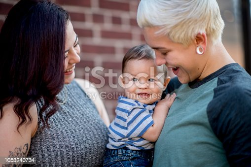 Same sex couple hold their baby son close to their chest as they smile at him. They are hugging their son tight as he smiles looking out into the distance.