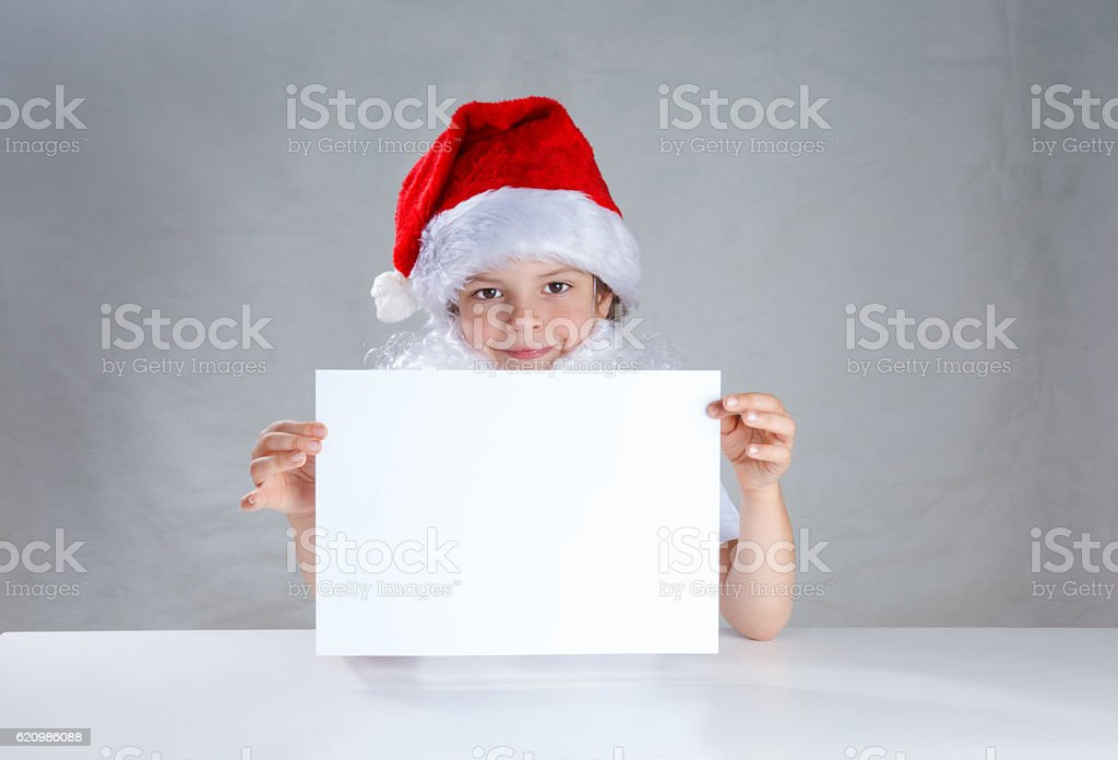 Young Santa holding a white sheet of paper and looking foto royalty-free