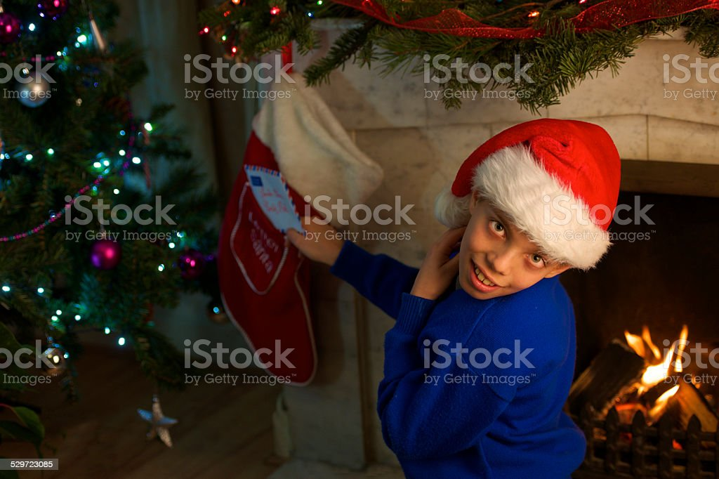 front to the fireplace young kid send Santa letter