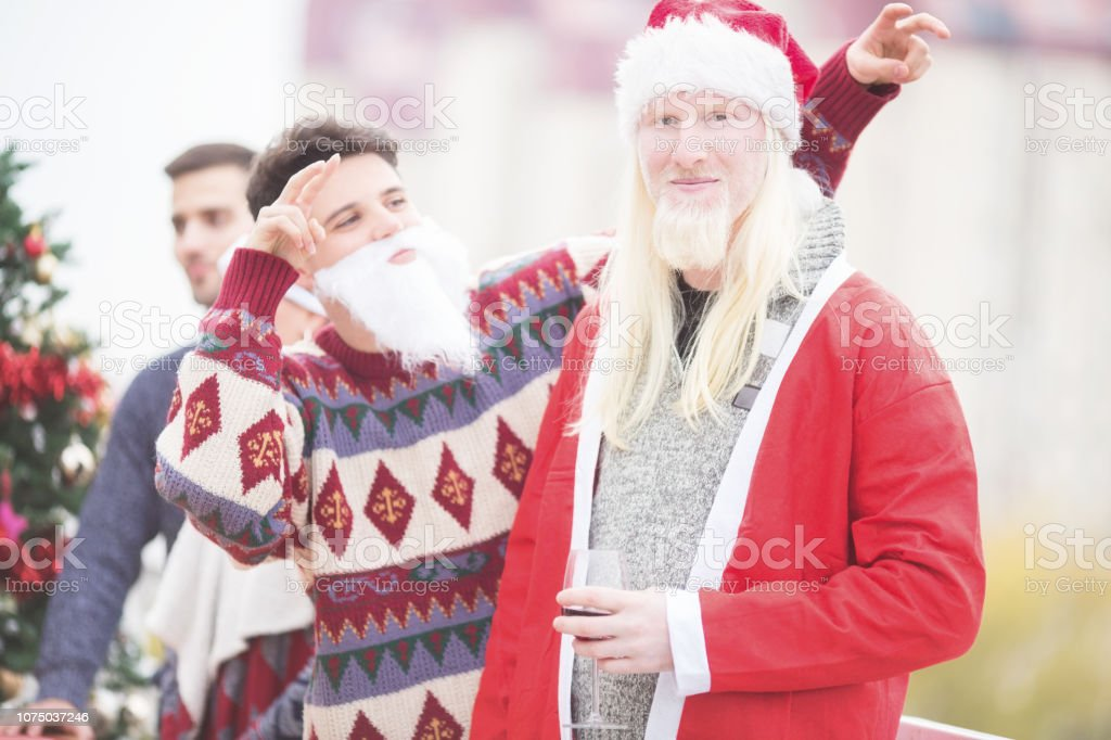 Young Santa man with friends on balcony celebrating Christmas stock photo