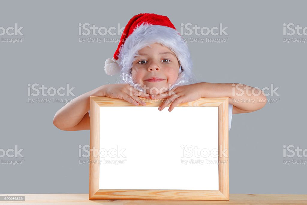 Young Santa put his head to an empty photo frame foto royalty-free