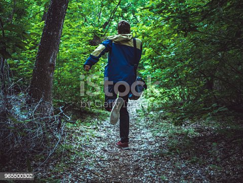 young scary man running away in the dark forest on the path back view