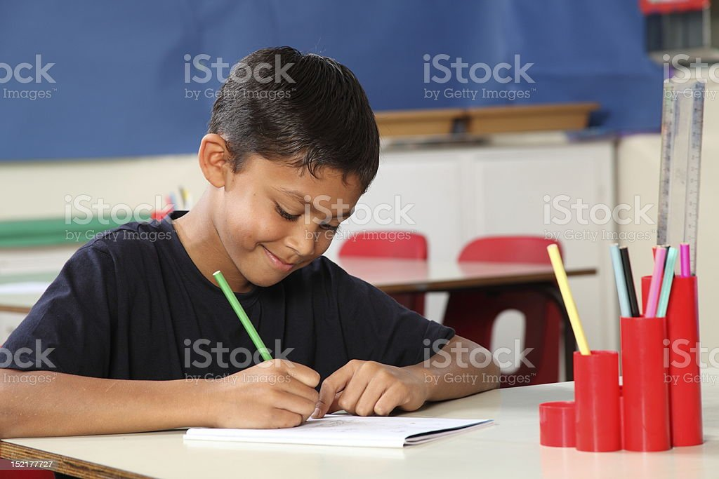 Young school boy 10 writing at his classroom desk stock photo