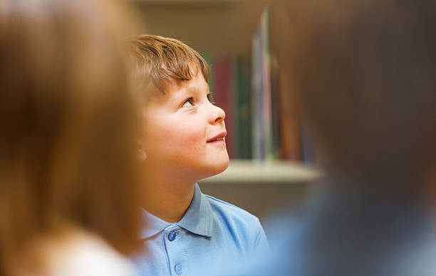 Young School Boy Listening in the Classroom stock photo