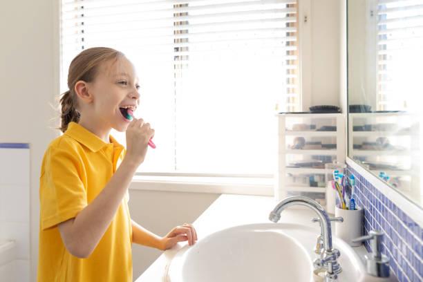 Ung skolflicka borsta tänder bildbanksfoto