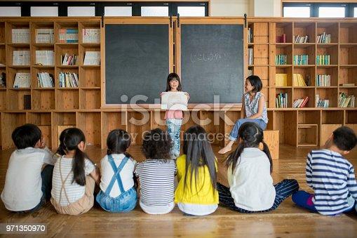 Young school girl giving a presentation in class. Okayama, Japan