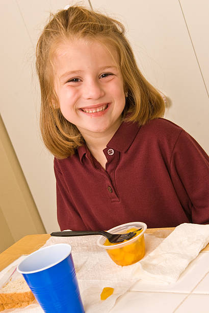 Young school girl smiling while eating lunch stock photo