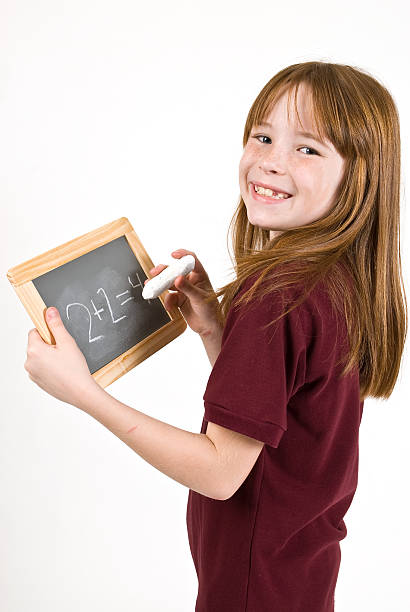 Young school girl writing on chalk board stock photo