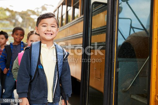1031397608 istock photo Young schoolboy and friends waiting to board the school bus 1031391130