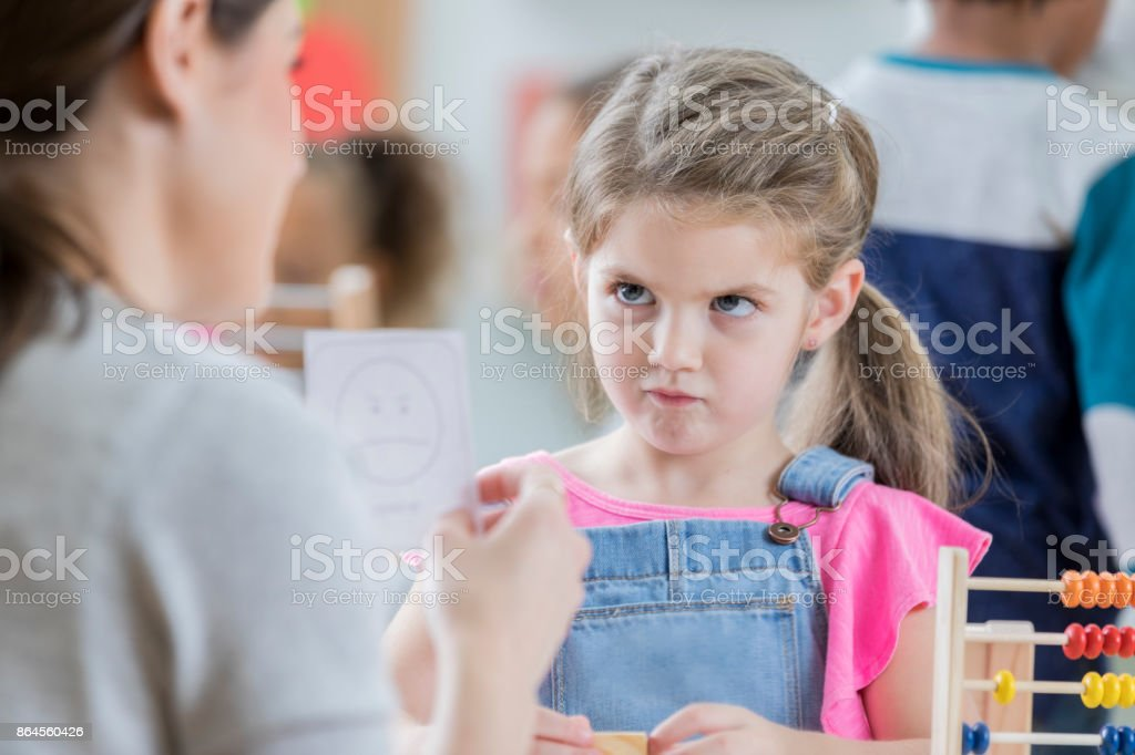 Young schoolgirl mimics face on emotion flash card stock photo