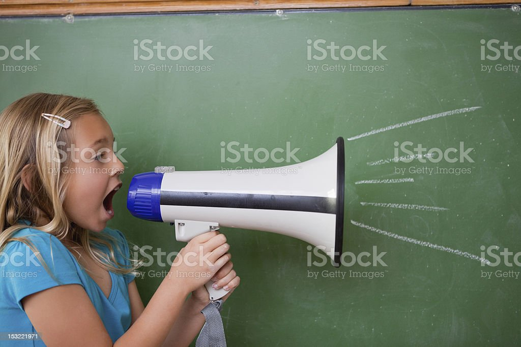 Young schoolgirl screaming through a megaphone royalty-free stock photo