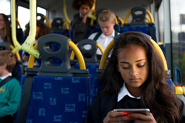 niña en edad escolar joven usando teléfono inteligente en autobús - autobuses escolares fotografías e imágenes de stock