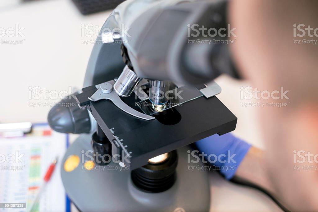Jonge wetenschapper op zoek door middel van een microscoop in een laboratorium - Royalty-free 20-24 jaar Stockfoto