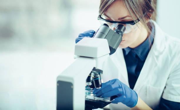 joven científico mirando a través de un microscopio en un laboratorio. joven científico haciendo algunas investigaciones. - investigación genética fotografías e imágenes de stock