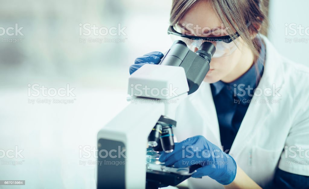 Young scientist looking through a microscope in a laboratory. Young scientist doing some research. stock photo