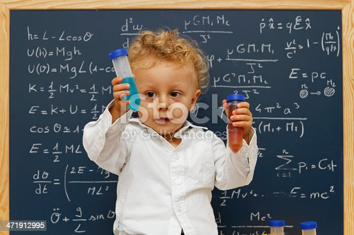 Young scientist front a blackboard with test tubes