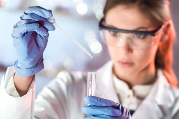 joven científico pipeteando en el laboratorio de ciencias de la vida. - biotecnología fotografías e imágenes de stock
